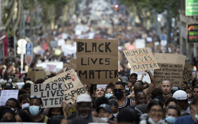 """A protester looks up at a sign that reads """"Black Lives Matter"""" in Marseille, southern France, during a protest against the recent death of George Floyd, June 6, 2020. (AP Photo/Daniel Cole, File)"""