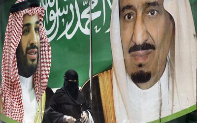 A woman walks past a banner showing Saudi King Salman, right, and his Crown Prince Mohammed bin Salman, outside a mall in Jiddah, Saudi Arabia, June 15, 2020. (AP Photo/Amr Nabil)