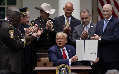 Law enforcement officials applaud after US President Donald Trump signed an executive order on police reform, in the Rose Garden of the White House, Tuesday, June 16, 2020, in Washington. (AP Photo/Evan Vucci)