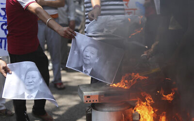 Indians burn photographs of Chinese President Xi Jinping during a protest against the Chinese government in Jammu, India, June 17, 2020. (/Channi Anand/AP)