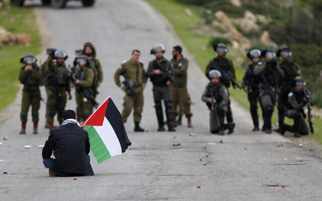 A Palestinian demonstrator holds a Palestinian flag in front of Israeli forces during a protest against US President Donald Trump's peace plan, in the Jordan Valley in the West Bank, on February 25, 2020. (AP Photo/Majdi Mohammed, File)