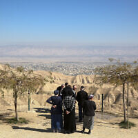 In this January 26, 2020 photo, Jewish settlers stand at a viewpoint overlooking the West Bank city of Jericho from the Jewish settlement of Mitzpe Yeriho (AP Photo/Oded Balilty)