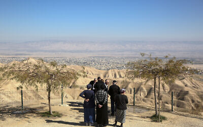 In this January 26, 2020, photo, Jewish settlers stand at a viewpoint overlooking the West Bank city of Jericho from the Jewish settlement of Mitzpe Yeriho (AP Photo/Oded Balilty)
