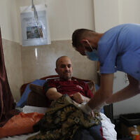 A Palestinian nurse checks cancer patient Jehad al-Qedra, 52, while he receives his treatment at a hospital in Khan Younis refugee camp, Gaza Strip, on June 16, 2020. (AP Photo/Adel Hana)