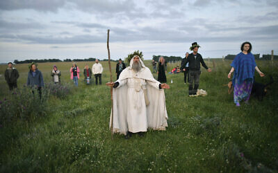 An Archdruid performs a ritual near the cordoned off Stonehenge as a small group of people gathered to celebrate the Summer Solstice, the longest day of the year, near Salisbury, England, June 21, 2020. (Ben Birchall/PA via AP)