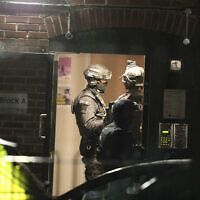 Armed police officers work at a block of flats off Basingstoke Road in Reading after a stabbing attack at Forbury Gardens park in the town center of Reading, England, June 20, 2020. (Steve Parsons/PA via AP)