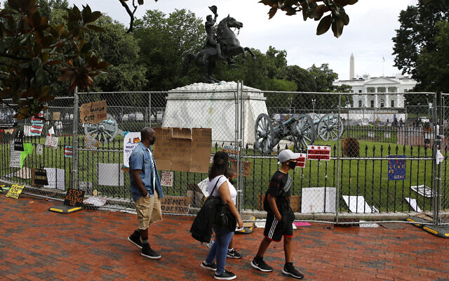 People wear face masks to protect against the spread of the new coronavirus as they walk past protest signs affixed to fencing surrounding a statue of President Andrew Jackson in Lafayette Park near the White House in Washington, June 20, 2020. (Patrick Semansky/AP)