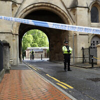 Police stand guard at the Abbey gateway of Forbury Gardens park in Reading town center following Saturday's stabbing attack in the gardens, June 21, 2020. (Jonathan Brady/PA via AP)