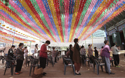 People wearing face masks to help protect against the spread of the new coronavirus pray while maintaining social distancing during a service at the Chogyesa temple in South Korea, June 22, 2020. (AP Photo/Ahn Young-joon)