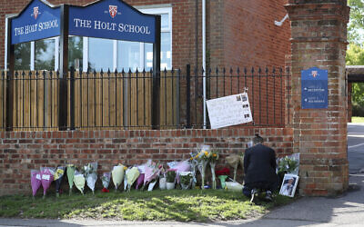 Flower tributes are placed at the entrance to Holt School in Wokingham, England, in memory of teacher James Furlong, a victim of a terror attack in nearby Reading, June 22, 2020. (Steve Parsons/PA via AP)