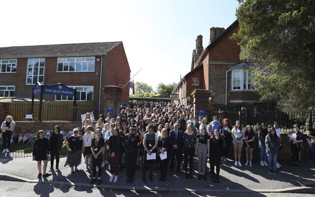 Colleagues and pupils of teacher James Furlong stand together to take part in a period of silence at the Holt School, in Wokingham, England, in memory of teacher James Furlong, a victim of a terror attack in nearby Reading, June 22, 2020. (Steve Parsons/PA via AP)