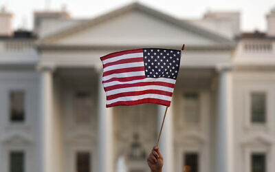 In this Sept. 5, 2017, file photo, a flag is waved outside the White House, in Washington. The Trump administration is extending a ban on green cards issued outside the United States until the end of 202 and adding many temporary work visas to the freeze, including those used heavily by technology companies and multinational corporations. (AP Photo/Carolyn Kaster, File)