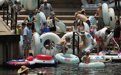 Tubers prepare to float the Comal River despite the recent spike in COVID-19 cases, Thursday, June 25, 2020, in New Braunfels, Texas. (AP Photo/Eric Gay)