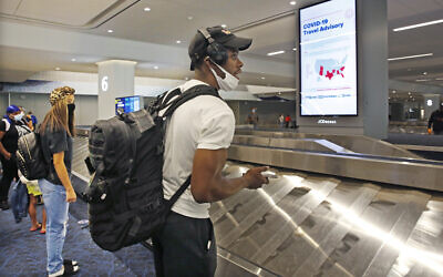Arriving passengers await their bags in the baggage claim area at LaGuardia Airport's Terminal B baggage claim area, June 25, 2020, in New York. (AP Photo/Kathy Willens)