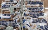 COVID-19 patients lie on beds in a field hospital built inside a gym in Santo Andre, on the outskirts of Sao Paulo, Brazil, June 9, 2020. (AP Photo/Andre Penner, File)