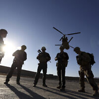 In this Nov. 30, 2017 file photo, American soldiers wait on the tarmac in Logar province, Afghanistan. Top officials in the White House were aware in early 2019 of classified intelligence indicating Russia was secretly offering bounties to the Taliban for the deaths of Americans, a full year earlier than has been previously reported.  (AP Photo/Rahmat Gul)