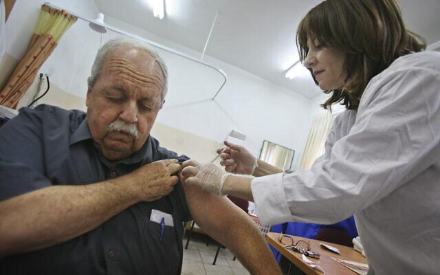 A man receives a swine flu vaccine at a medical center in Jerusalem, December 20, 2009 (AP Photo/Dan Balilty)