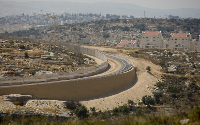 A section of Israel's security barrier between the Jewish settlement of Modiin Illit, right, and the outskirts of the West Bank village of Bilin, near Ramallah, June 23, 2011. (AP Photo/Ariel Schalit)