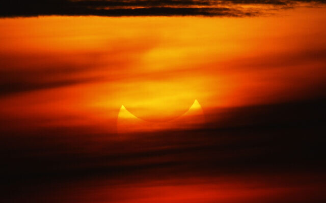 """A """"ring of fire"""" solar eclipse is partially seen at sunrise, May 21, 2012, from the coastal township of Gumaca, Quezon province, 187 kilometers (116 miles) southeast of Manila, Philippines. (AP Photo/Bullit Marquez)"""