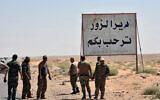 "This file photo released Sept. 3, 2017, by the Syrian official news agency SANA, shows Syrian troops and pro-government gunmen standing next to a sign in Arabic which reads, ""Deir el-Zour welcomes you,"" in the eastern city of Deir el-Zour, Syria. (SANA via AP)"
