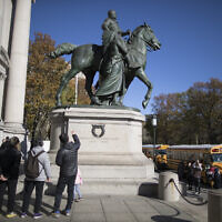 In this Nov. 17, 2017 file photo, visitors to the American Museum of Natural History in New York look at a statue of Theodore Roosevelt, flanked by a Native American man and African American man. The statue will be coming down after the museum's proposal to remove it was approved by the city (AP Photo/Mary Altaffer)