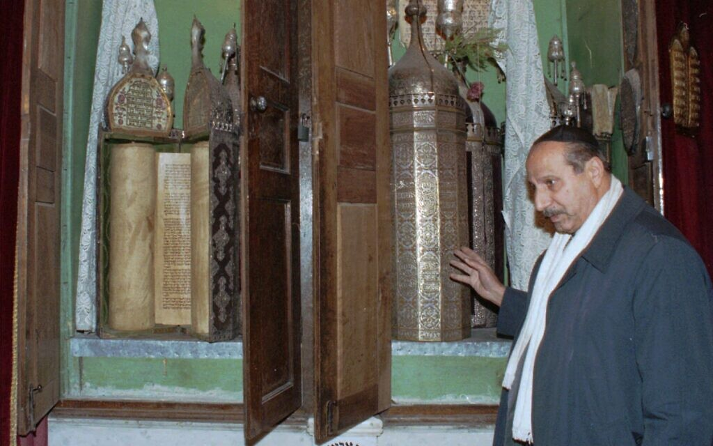 FILE - This Friday, January 21, 2000, file photo, Youssef Jajati, a Jewish community leader in Syria, points out the Torah holy book preserved in a silver container in Joubar's Synagogue which dates back to 718 BCE. (AP Photo/ Bassem Tellawi, File)