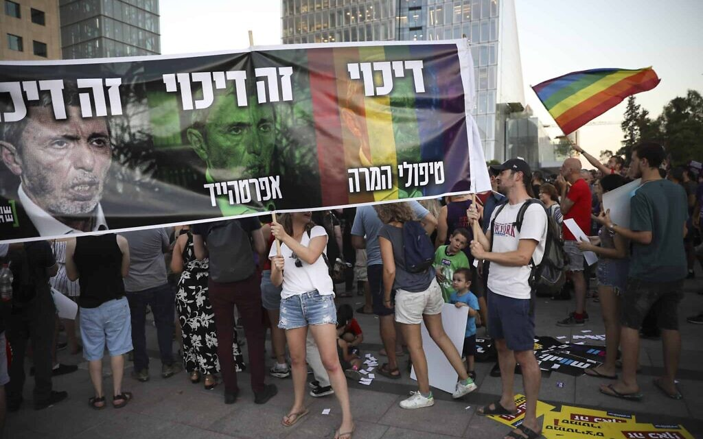 A 2019 rally against gay conversion therapy, with demonstrators holding a sign featuring MK Rafi Peretz and the words 'Oppression is Oppression.' (AP Photo/Oded Balilty)