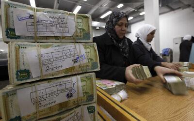 Employees stack Syrian currency in the Central Bank, in Damascus, Syria, January 13, 2010. (Hussein Malla/AP)