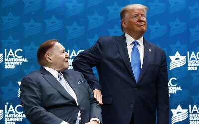 US President Donald Trump pats Las Vegas Sands Corporation Chief Executive and Republican mega donor Sheldon Adelson on the arm before speaking at the Israeli American Council National Summit in Hollywood, Florida, December 7, 2019. (Patrick Semansky/AP)