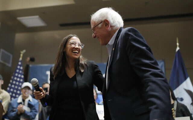 US Senator Bernie Sanders, right, laughs with Rep. Alexandria Ocasio-Cortez, at a campaign event on Jan. 26, 2020, in Storm Lake, Iowa. (AP Photo/John Locher)