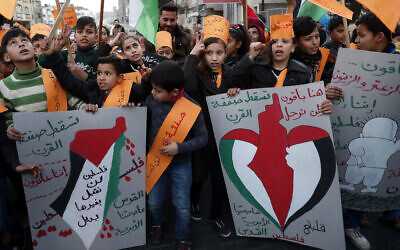 Protesters hold placards as others wave their national flags during a protest against the Mideast plan announced by the US President Donald Trump, at Jebaliya refugee camp, Gaza Strip, January 30, 2020. (Adel Hana/AP)