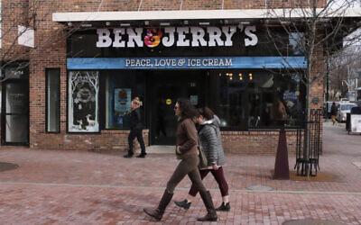 Pedestrians walk on Church St., past the Ben & Jerry's shop, in Burlington, Vermont, March 11, 2020. (AP Photo/Charles Krupa)