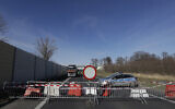 Polish policemen talk to a driver at the closed border crossing near Hradek nad Nisou, Czech Republic, March 15, 2020. (AP Photo/Petr David Josek)