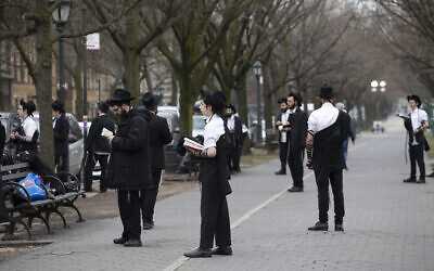 Illustrative: Orthodox Jewish men use social distancing as they pray outside the Chabad Lubavitch World Headquarters, Friday, March 20, 2020 in the Brooklyn borough of New York. (AP Photo/Mark Lennihan)