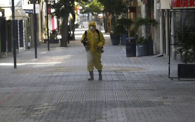 A municipality worker wearing a protective suit sprays disinfectant a deserted pedestrian main street in central Nicosia, Cyprus, Wednesday, March 25, 2020. (AP/Petros Karadjias)
