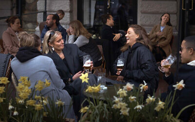 In this April 8, 2020, photo people chat and drink outside a bar in Stockholm, Sweden. Sweden is pursuing relatively liberal policies to fight the coronavirus pandemic, even though there has been a sharp spike in deaths. (AP Photo/Andres Kudacki, File)