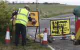 A worker removes a swastika spray painted on a sign at the entrance to a closed road and car park near Whitley Bay lighthouse, in Northumberland, England, Thursday, April 30, 2020.  (Owen Humphreys/PA via AP)