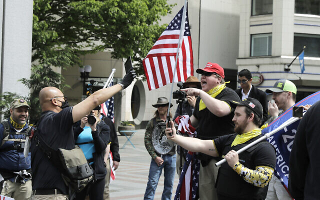 Illustrative -- Members of a group wearing shirts with the logo of the far-right Proud Boys group at right, argue with a counter protester during a small protest against Washington state's stay-at-home orders, May 1, 2020, in downtown Seattle (AP Photo/Ted S. Warren)