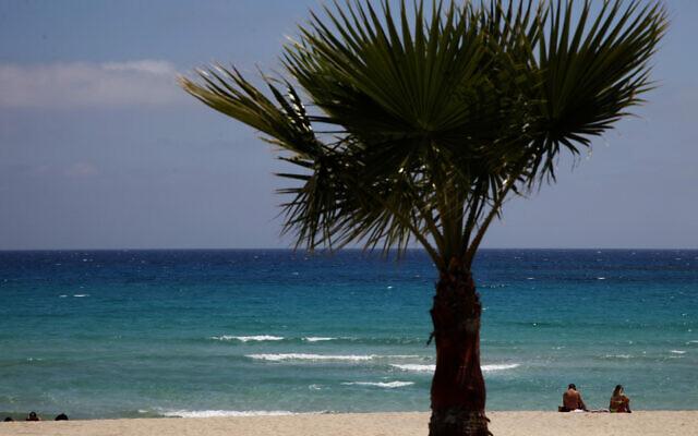 Sunbathers sit on an empty stretch of 'Landa' beach at the Cyprus seaside resort of Ayia Napa, a favorite among tourists, May 10 2020. (Photo/Petros Karadjias)