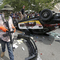 An armed protester in a Hawaiian shirt walks past a flipped over police vehicle Saturday, May 30, 2020, in Salt Lake City.  (AP/Rick Bowmer)