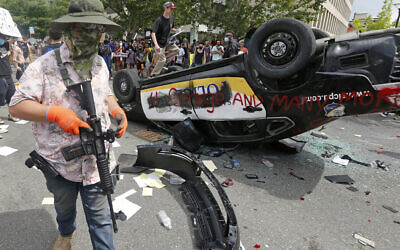 An armed protester in a Hawaiian shirt walks past a flipped over police vehicle Saturday, May 30, 2020, in Salt Lake City.  (AP/Rick Bowmer)