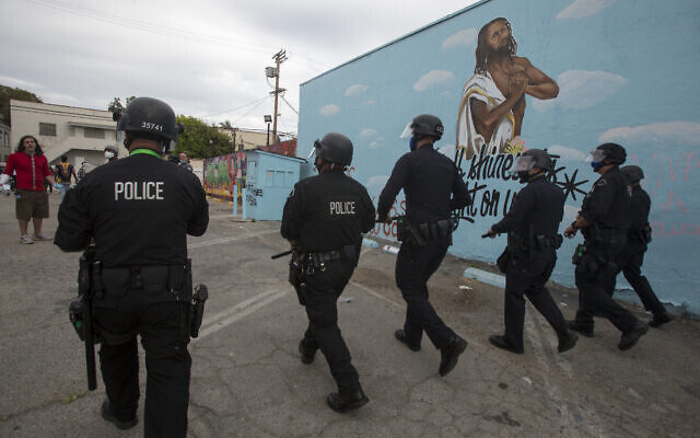 Police officers move forward during a protest over the death of George Floyd, a handcuffed black man in police custody in Minneapolis, in Los Angeles, Saturday, May 30, 2020. (AP Photo/Ringo H.W. Chiu)