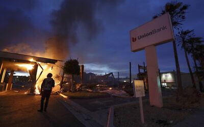 A man looks on as a bank burns after a protest over the death of George Floyd, May 31, 2020, in La Mesa, Calif. Protests were held in US cities over the death of Floyd, a black man who died after being restrained by Minneapolis police officers on May 25. (AP Photo/Gregory Bull)