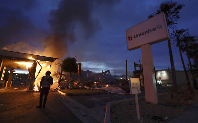 A man looks on as a bank burns after a protest over the death of George Floyd, Sunday, May 31, 2020, in La Mesa, Calif. Protests were held in U.S. cities over the death of Floyd, a black man who died after being restrained by Minneapolis police officers on May 25. (AP Photo/Gregory Bull)