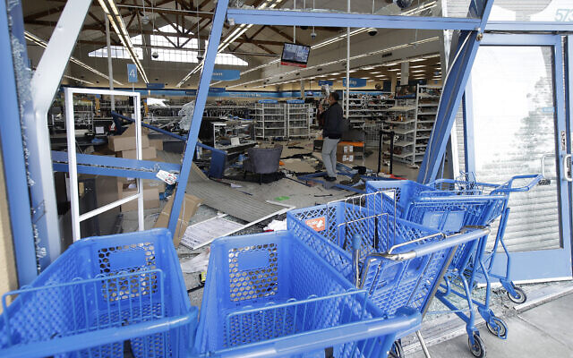 A man walks inside a damaged Ross Dress For Less store in Emeryville, Calif., Sunday, May 31, 2020, after protests over the Memorial Day death of George Floyd. Floyd was a black man who was killed in police custody in Minneapolis on May 25. (AP Photo/Jeff Chiu)