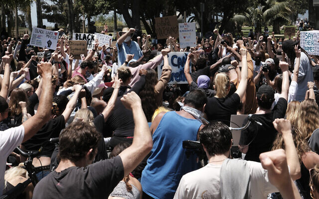 Protesters raise their fists and take to their knees in prayer during a Black Lives Matter protest while blocking traffic on a street corner in Santa Monica, Calif. on Sunday, May 31, 2020, over the death of George Floyd, a black man who was in police custody in Minneapolis. Floyd died after being restrained by Minneapolis police officers on Memorial Day. (AP Photo/Richard Vogel)