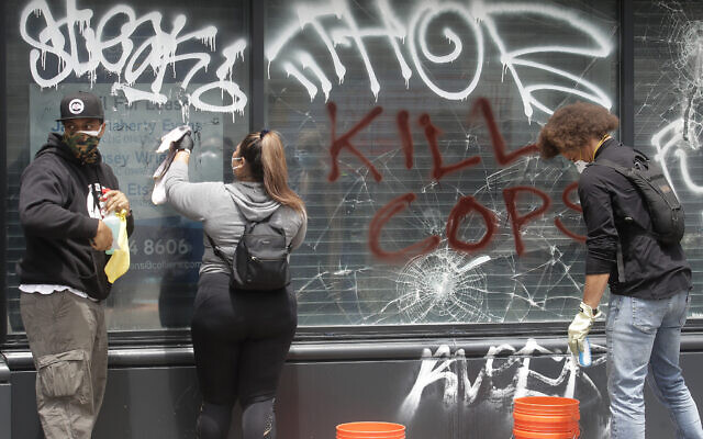 People with OccupyLove WorldWide clean graffiti off of windows in Oakland, Calif., Sunday, May 31, 2020, after protests over the Memorial Day death of George Floyd. Floyd was a black man who was killed in police custody in Minneapolis on May 25. (AP Photo/Jeff Chiu)
