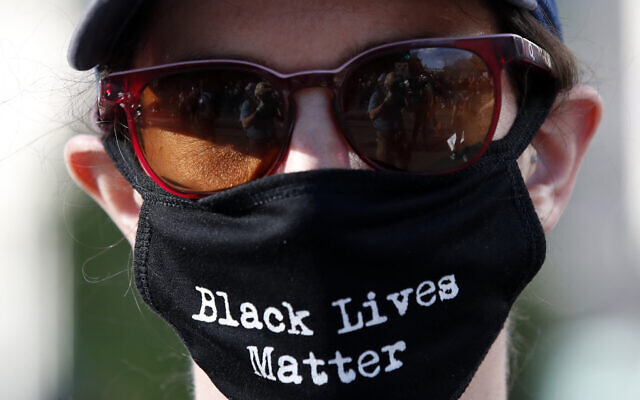 A US demonstrator wears a face mask during a protest over the death of George Floyd, May 31, 2020, near the White House in Washington. (AP Photo/Alex Brandon)