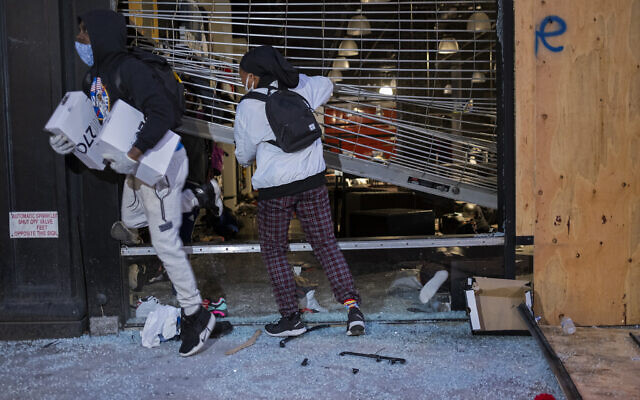 People exit damaged stores after the glass was knocked out in the Chelsea neighborhood of New York, Monday, June 1, 2020. (AP Photo/Craig Ruttle)