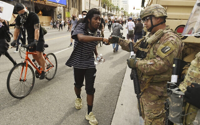 A protest rally participant bumps fists with a National Guardsman on Hollywood Boulevard, Tuesday, June 2, 2020, in Los Angeles. Protests were held in US cities over the death of George Floyd, a black man who died after being restrained by Minneapolis police officers on May 25. (AP Photo/Chris Pizzello)